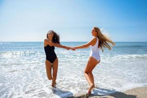 Two women in swimsuit having fun on the beach photo