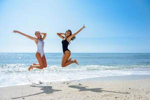 Two funny girls in swimsuit jumping on a tropical beach photo