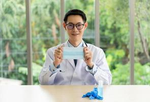 asian doctor wearing white coat showing surgical mask and advice people to use it for protection of covid-19 or coronavirus infection. healthcare and medical concept photo