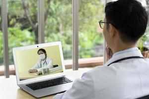 El médico asiático consulta a su colega en línea a través de una videoconferencia sobre el plan de tratamiento del paciente. concepto de telemedicina foto