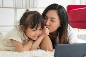 niño asiático besando a su madre mientras la madre usa la tableta para tomarles una foto en la sala de estar. concepto de familia unida
