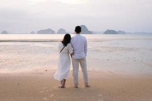 young married couple standing at the beach and looking at sunset on honeymoon vacation. togetherness concept photo