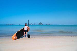 young sporty woman playing stand-up paddle board on the blue sea in sunny day of summer vacation photo