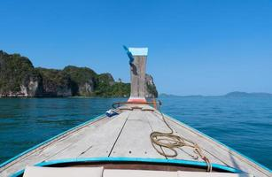 the bow of long tail boat riding on blue sea in sunny day of summer season photo