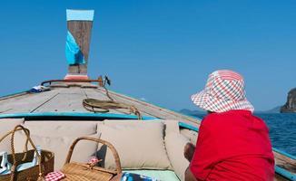senior man sitting on the boat and enjoying blue ocean on summer vacation photo