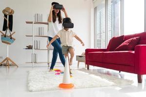 niño asiático joven y mamá jugando al juego de realidad virtual en casa. concepto de familia unida foto