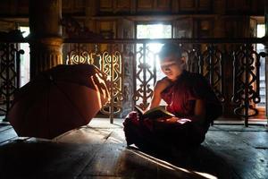 Joven monje novicio asiático leyendo un libro en el monasterio foto