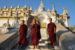 Grupo de monje novicio asiático bajando las escaleras del monasterio foto