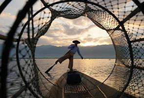 view through fish coop of local fisherman standing on boat in lake at sunrise photo