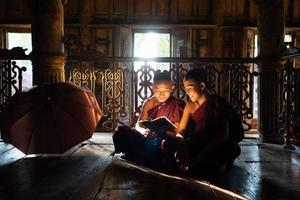 Dos jóvenes monjes novicios asiáticos leyendo un libro en el monasterio juntos foto
