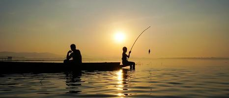 At lake side, asian fisherman sitting on boat while his son standing and  using fishing rod to catch fish at the sunrise photo