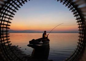At lake side, asian fisherman sitting on boat and using fishing rod to catch fish at the sunrise photo