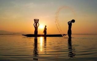 Silhouette of fisherman and his son standing in the lake near boat and using jar to splash water photo