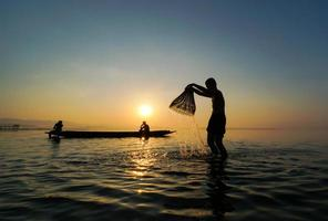 asian fisherman standing on boat and using fishing rod to catch fish while his son splashing water to each other at lake side in morning photo