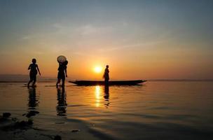 Pescador asiático de pie en el barco y usando caña de pescar para pescar mientras su hijo sostiene una trampa de bambú y corre al lado del lago en la mañana foto