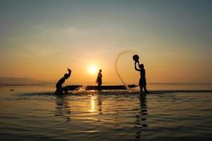 Pescador asiático de pie en el barco y usando caña de pescar para pescar mientras su hijo se salpica agua el uno al otro al lado del lago en la mañana foto