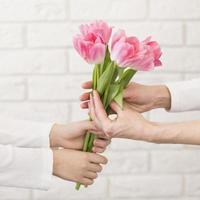 niño ofreciendo flores madre foto