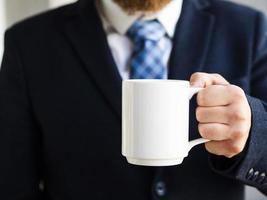 elegant man holding up white mug photo