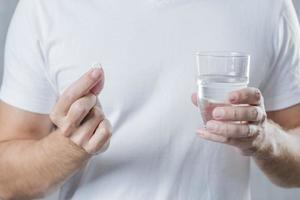 close up man s hand holding white pill glass water hand photo