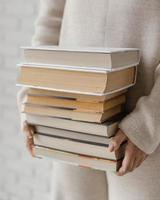 close up hands holding books stack photo
