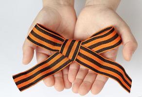 St. George's ribbon loop isolated on white background. Black and orange ribbon. photo