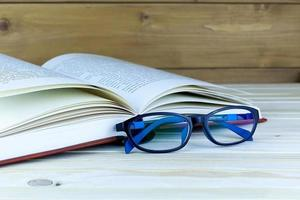 Spectacles on top of a book. Green nature background photo