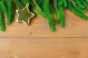 Natural spruce branches with a gold star on a wooden background. photo