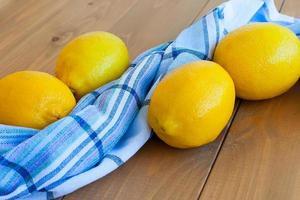 Bodegón de grandes limones amarillos maduros acostado sobre una toalla a cuadros con un vaso de jugo de limón en el alféizar de la ventana en la habitación iluminada por el sol. foto
