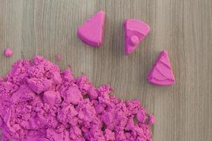 bright pink kinetic sand in the hands of a child. Development and education. Fine motor skills photo