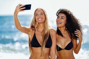 Two women taking selfie photograph with smartphone in the beach photo