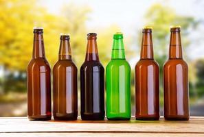 Botellas de cerveza de colores en la mesa sobre fondo borroso forrest, concepto de vacaciones foto