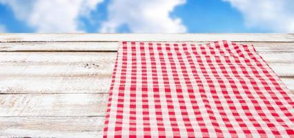 Mantel rojo sobre la mesa de madera vacía, fondo de cielo borroso foto