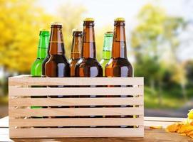 Botellas de cerveza artesanal en la caja de la mesa de madera en el fondo del parque borrosa foto