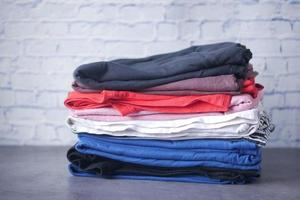 close up of stack of clothes on table . photo