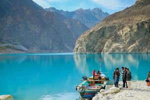 Gilgit Baltistan, Pakistan,2017 - People going to rent a colorful boat at Attabad lake, with a view of mountains in Karakoram range and turquoise still water. Gojal Hunza. photo