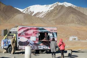 Khunjerab Pass, Pakistán, 2017 - Mujeres turistas hablando con un hombre vendiendo comida en la frontera entre Pakistán y China. foto