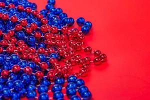 Christmas background. Beads in red and blue on a red background. New Year. photo