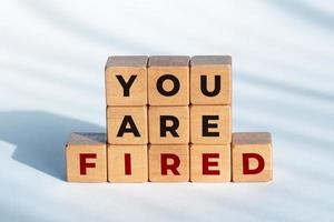 You are fired phrase on wooden dices. Unemployment concept photo