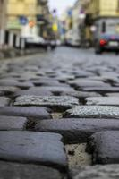 Old historic cobbled high street with selective focus on cobble stones photo