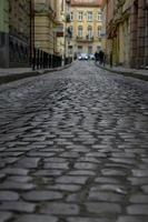 Old cobbled high street with selective focus on cobble stones photo