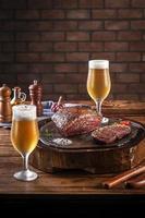 Bistec de grupa a la parrilla sobre tabla de cortar de madera con dos vasos de cerveza tulipa fría sudorosa. mesa de madera y fondo de pared de ladrillos - picanha brasileña. foto