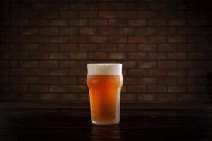 Isolated sweaty glass of refreshing ale draft beer with brick wall background. photo