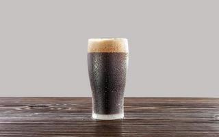 Isolated sweaty glass of refreshing dark draft beer with white background. photo