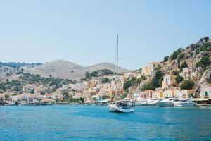 Yatch arriving at Symi harbour. View of the colorful village on a summer day. Greece photo