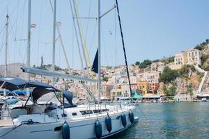 White yacht arriving to colorful Symi harbour on a sunny day. Greece. photo