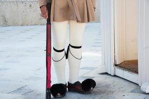 Greek guard with typical uniform at Syntagma Square wearing his Gtsarouchia, the traditional shoes of Evzones which are red with a small tuft in front. photo