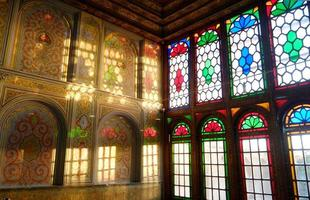 Shiraz, Iran,2016 - Beautiful interior room lit with sun rays through colorful stained glass windows reflecting colors on the wall in Qavam House or Narenjestan e Ghavam photo