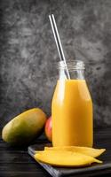 fresh mango shake in a glass with a metal drinking straw decorated with slices of mango front view on dark background photo