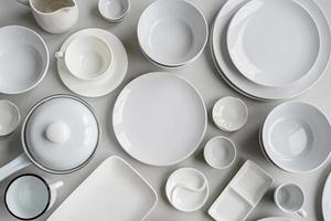 piles of white ceramic dishes and tableware top view on gray background photo