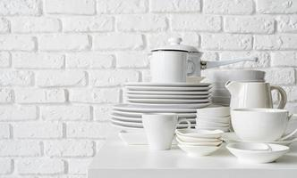 stack of white ceramic dishes and tableware on the table on white brick wall background photo